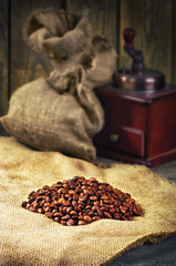 coffee beans, hand grinder on sacking in vintage grunge style