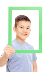Cute little boy posing behind a picture frame