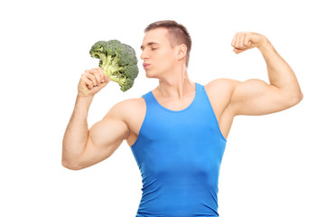 Muscular man kissing a huge piece of broccoli