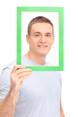 Young man posing behind a green picture frame
