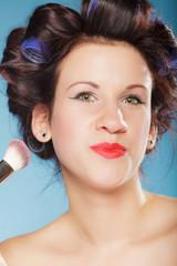 woman applying rouge blush makeup