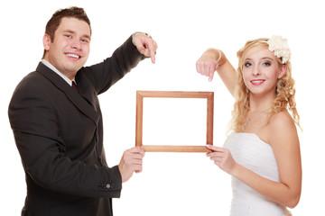 wedding couple pointing empty frame for photo.