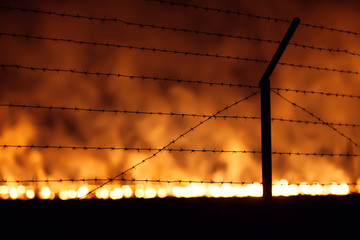 Night fire in a field view through Barbed wire