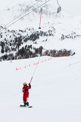Little girl snowboarder rises up on ski-tow in French Alps