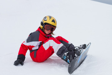 Little girl snowboarder sitting at ski slope  in French Alps