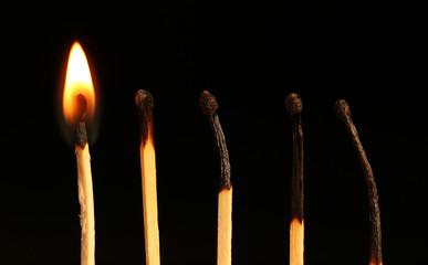 Burnt and burning matches on black background