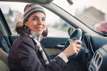 Portrait of smiling young woman sitting in a car