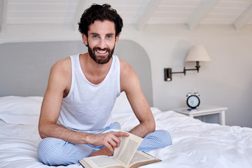 portrait of man book relaxing bed
