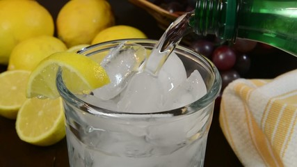 Pouring sparkling water into a glass with lemon wedges