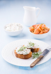 Canapes with soft cheese spread on white plate
