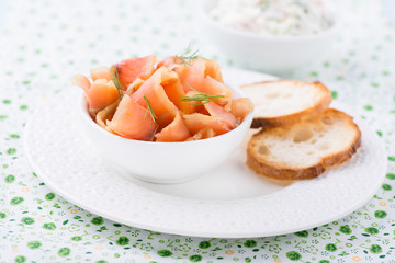 Smoked wild salmon and baguette on white plate