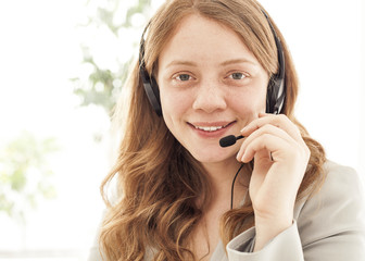 Portrait of happy young female with headset