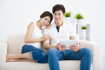 happy young Couple on sofa with tablet