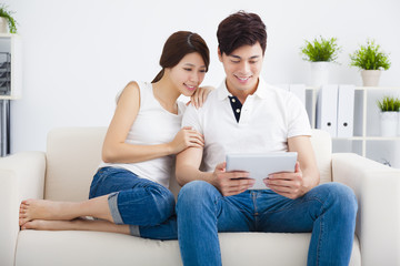 asian Couple on sofa with tablet computer