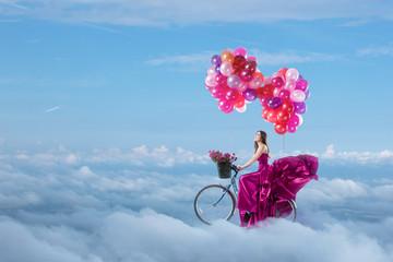 Woman in beautiful dress flying on her bike