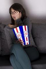Girl watching terror film with popcorn