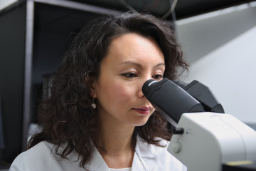 Asian female scientist at microscope