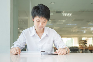 Asian student in uniform reading book at the classroom