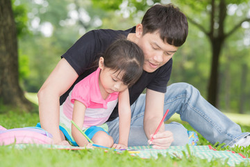 Happy kid and dad paint together in park