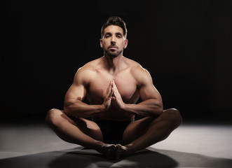 Topless Muscular Man Sitting in a Yoga Position