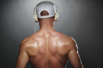 Back View of Muscular Man with Cap and Headphones