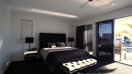 Panning shot of a large master bedroom in a luxury house