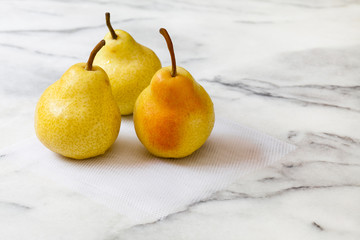 Yellow pears on white marble kitchen counter, with white netting