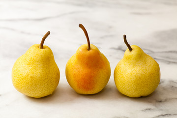 Yellow pears in a row on white marble kitchen counter