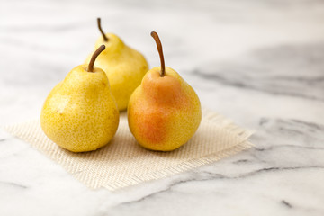 Yellow pears on white marble counter with burlap square
