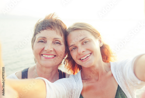 mother and adult daughter are doing Selfe on the beach - 79715303