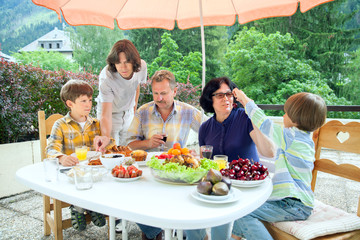 The family from five persons have got dinner on summer terrace