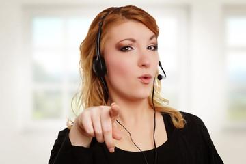 junge Frau mit Headset zeigt in die Kamera