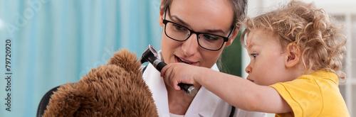 Leinwanddruck Bild Little boy using otoscope