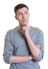 Junger Mann im grauen Shirt denkt nach