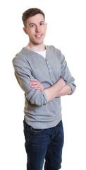 Stehender junger Mann im grauen Shirt mit verschränkten Armen