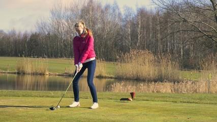 Frau beim Abschlag auf einem Golfplatz