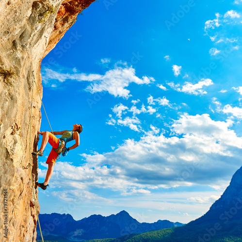 Rock climber climbing up a cliff - 79723544