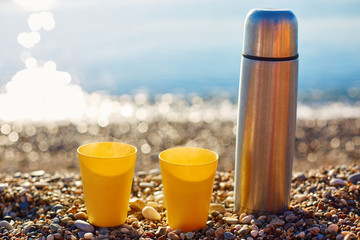 two yellow cups on a sunny beach