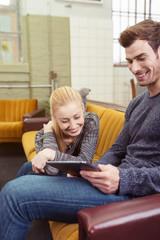 lachendes paar schaut sich etwas am tablet an