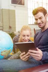 paar plant eine reise und informiert sich am tablet