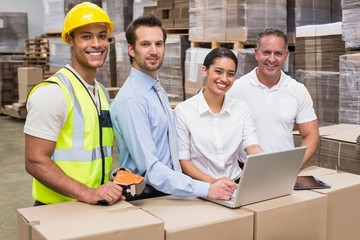 Warehouse managers and worker looking at camera