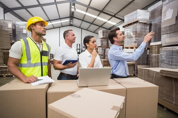 Warehouse manager pointing something to his colleagues