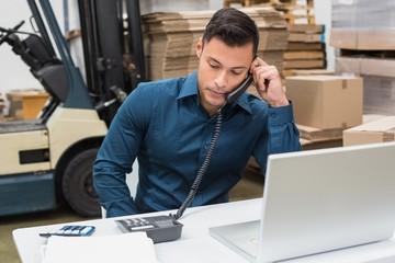 Warehouse manager using telephone and laptop