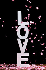 Falling pink confetti on love word