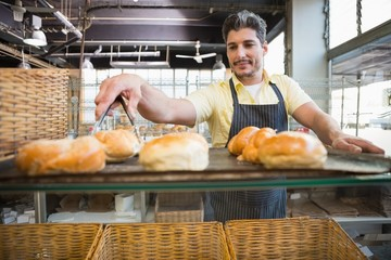 Smiling waiter taking bread with tongs