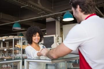 Smiling waiter doing transaction with customer