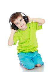 little boy listening to music through big headphones