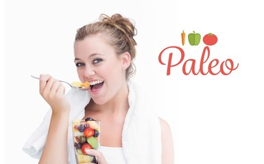 Paleo against woman eating fruit and smiling