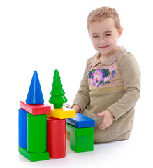 cute little girl sitting on the floor and playing with blocks