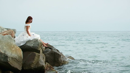 Beautiful Woman In White Dress Sitting On Rock By Sea